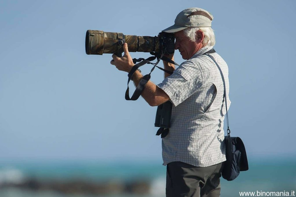 Gian Pietro Pittaluga fotografa con un teleobiettivo in Liguria